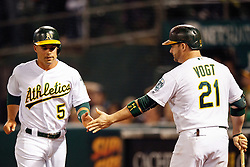 OAKLAND, CA - SEPTEMBER 09:  Jake Smolinski #5 of the Oakland Athletics is congratulated by Stephen Vogt #21 after scoring a run against the Seattle Mariners during the fifth inning at the Oakland Coliseum on September 9, 2016 in Oakland, California. The Seattle Mariners defeated the Oakland Athletics 3-2. (Photo by Jason O. Watson/Getty Images) *** Local Caption *** Jake Smolinski; Stephen Vogt