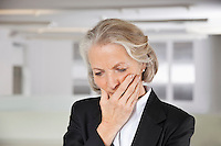 Worried senior businesswoman with hand on mouth in office