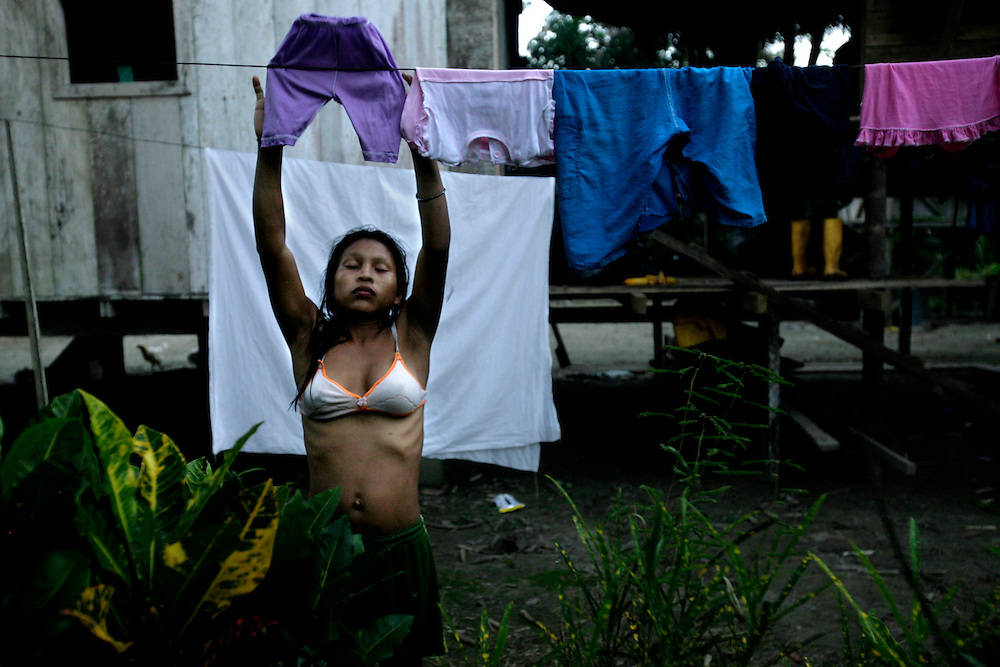 Lorena Grefa washes her family clothes. In the Kichwa families all the kids help out, be it harvesting, fishing or taking care of the younger kids. Lorena lives with his parents and her little baby while her husband comes back from enlisting in the military services for two years.