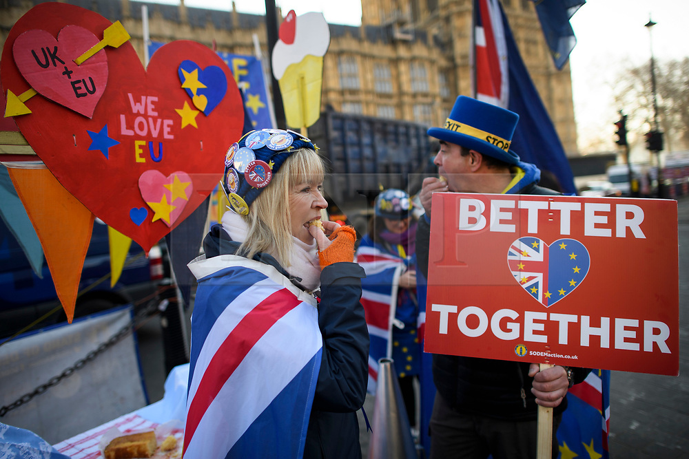 © Licensed to London News Pictures. 14/02/2019. London, UK. Anti Brexit campaigners eat cake outside the Houses of Parliament in Westminster, on the day that MPs are due to take part in further debates and votes on Brexit. A series of amendments are being tabled to try to change the direction of Brexit, but a vote on a deal will not be held today as was originally planned. Photo credit: Ben Cawthra/LNP
