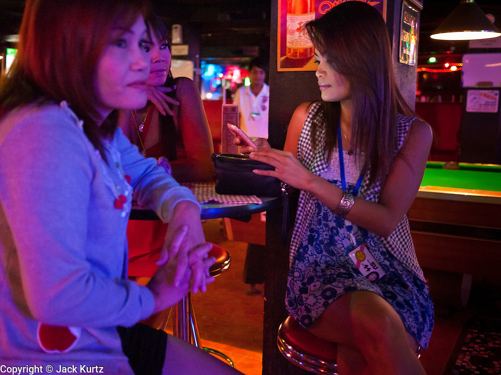 "12 JULY 2011 - BANGKOK, THAILAND:  Women in the ""Corner Bar"" on Soi Cowboy in Bangkok. Soi Cowboy is a ""red light"" district that is home to several brothels and ""short time"" hotels that charge by the hour for their rooms. Prostitution in Thailand is illegal, although in practice it is tolerated and partly regulated. Prostitution is practiced openly throughout the country. The number of prostitutes is difficult to determine, estimates vary widely. Since the Vietnam War, Thailand has gained international notoriety among travelers from many countries as a sex tourism destination. One estimate published in 2003 placed the trade at US$ 4.3 billion per year or about three percent of the Thai economy. It has been suggested that at least 10% of tourist dollars may be spent on the sex trade. According to a 2001 report by the World Health Organisation: ""There are between 150,000 and 200,000 sex workers (in Thailand).""  PHOTO BY JACK KURTZ"