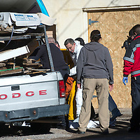 Richard Malone, with the Office of Medical Investigator, helps remove the body of a man who died inside the cabin of a Dodge truck off South Eight Street in Gallup Wednesday.
