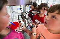 Broken Bow fifth-grader Harley Elder tests the suction of a milking machine by sticking it to his face while exploring the Nebraska Builuding with his classmates Macy Doggett, far left, and Jace Applegarth-Baxter, right, during the Nebraska State Fair in Grand Island.