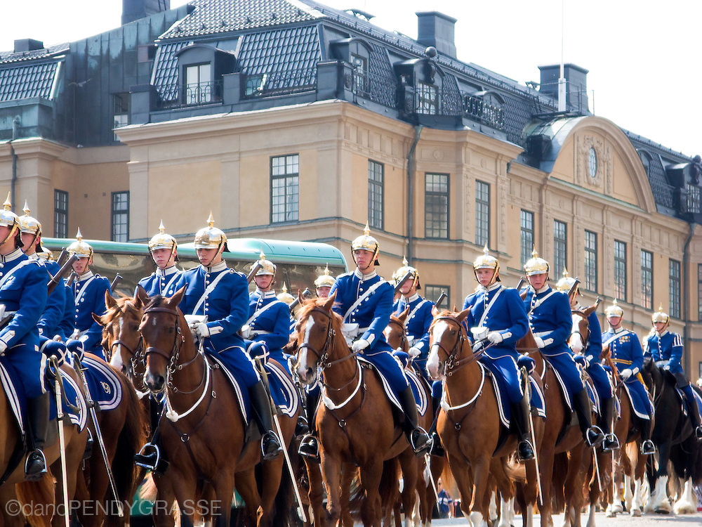 Military cadets ride horseback in front of the Royal Palace in Stockholm.