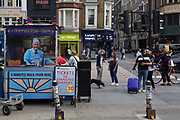 A couple hug and the rear of a newspaper vendor's kiosk outside Liverpool Street mainline station in the City of London - the capital's financial district, on 3rd September 2018, in London England.