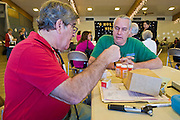 08 DECEMBER 2010 - PHOENIX, AZ: Dr. CHARLES LEVISON (red shirt) talks to STEVE HOLLINGSWORTH, a patient at a Mission of Mercy mobile clinic in Phoenix, AZ, Wednesday, Dec. 8. Mission of Mercy has been providing free medical help for people in the Phoenix area since 1997. In the last two years, as the Arizona economy continued its recessionary slide, patient load at the clinics has more than doubled. Mission of Mercy, which relies on voluntary medical help and financial donations, recently acquired another mobile clinic so they could expand their reach into suburban areas they previously had not served. Mission of Mercy has provided free medical help to more than 43,000 patients in the Phoenix area since 1997.    PHOTO BY JACK KURTZ