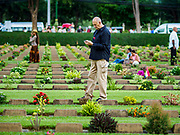 "11 NOVEMBER 2018 - KANCHANABURI, KANCHANABURI, THAILAND: People walk through the Kanchanaburi War Cemetery during the Rememberance Day ceremony in Kanchanaburi, Thailand. Kanchanaburi is the location of the infamous ""Bridge On the River Kwai"" and was known for the ""Death Railway"" built by Japan during World War II using allied, principally British, Australian and Dutch, prisoners of war as slave labor. There are 6,982 people buried in the cemetery, including 5,000 Commonwealth soldiers and 1,800 Dutch soldiers. November 11, 2018 marked the 100th anniversary of the end of World War I, celebrated as Rememberance Day in the UK and the Commonwealth and Veterans' Day in the US.    PHOTO BY JACK KURTZ"
