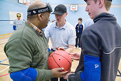Coach talking to Team members who are holding a ball during a Goalball training; a threeaside game developed for the visually impaired and played on a volleyball court, A specially adapted ball containing an internal bell is used,