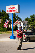 "03 AUGUST 2020 - JEWELL, IOWA: A man with his daughter on his shoulders walks to the Jewell Market. The only grocery store in Jewell, a small community in central Iowa, closed in 2019. It served four communities within a 20 mile radius of Jewell. Some of the town's residents created a cooperative to reopen the store. They sold shares to the co-op and  held fundraisers through the spring. Organizers raised about $225,000 and bought the store, which had its ""soft opening"" July 8. The store celebrated its official reopening Monday August 3. Before the reopening, Jewell had been a ""food desert"" for seven months. The USDA defines rural food deserts as having at least 500 people in a census tract living 10 miles from a large grocery store or supermarket. There is a convenience store in Jewell, but it sells mostly heavily processed, unhealthy snack foods that are high in fat, sugar, and salt.        PHOTO BY JACK KURTZ"