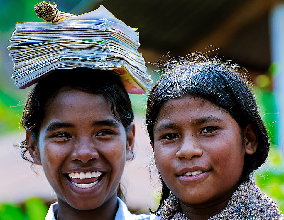 A happy smiling school girl with her friend is carrying her  books and papers on her head on Lembata Island, Indonesia.