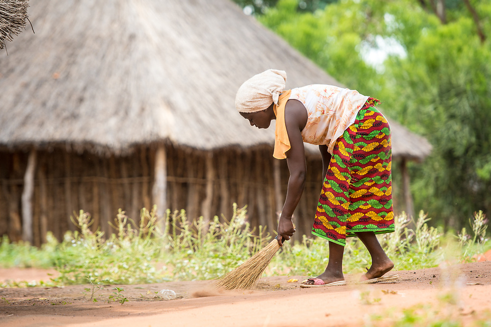 Zambian woman in traditional patterned skirt uses hand broom to sweep up litter that has been discarded onto ground, Mukuni Village, Zambia