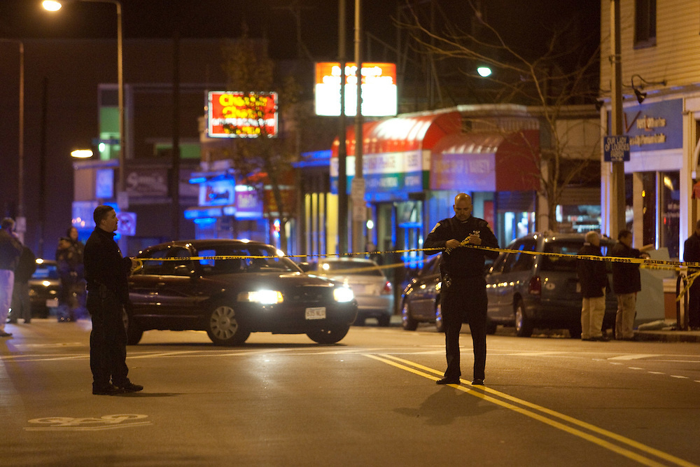 Boston, MA 11/21/2010.Boston Police officers string crime scene tape across Centre St. after a shooting inside the Same Old Place restaurant in Jamaica Plain on Sunday evening..Alex Jones / www.alexjonesphoto.com
