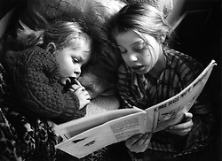 Young girl lying in bed reading bedtime story to younger sister,