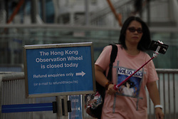 September 6, 2017 - Hong Kong, CHINA - Woman try to take a selfie as she walk out of cordoned venue of Hong Kong Observation Wheel at Central. Hong Kong Observation Wheel managed by current operator SWISS AEX stopped operating last week without prior announcement because of the payment dispute. SWISS AEX is required to dismantle the Ferris wheel tomorrow Sept 7, 2017 HK Time if, new operator THE ENTERTAINMENT CORP LTD ( TECL ) fail to attain relevant permits from Hong Kong Government to continue with the business.Sept 6, 2017.Hong Kong.ZUMA/Liau Chung Ren (Credit Image: © Liau Chung Ren via ZUMA Wire)