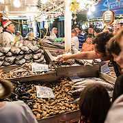 Customers buying fresh seafood at Mercado Central de Santiago, Chile's central market. The market specializes in seafood, a staple food category of Chilean cuisine. The building is topped with an ornate cast-iron roof.