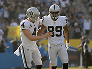 Dec 31, 2017; Carson, CA, USA; Oakland Raiders quarterback Derek Carr (4) and wide receiver Amari Cooper (89) celebrate after a touchdown in the second quarter against the Los Angeles Chargersduring an NFL football game at StubHub Center.