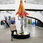 "March 10, 2012 - New York, NY : Alexandra Kucharz, 6, center, and Bruno Spampinato, 3, center left, play beneath a hanging yarn puppet created by Misaki Kawai -- part of Kawai's installation ""Love from Mt. Pom Pom"" -- at the Children's Museum of the Arts in the south village on March 10. CREDIT: Karsten Moran for The New York Times"