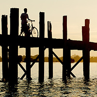 People crossing the U Bein bridge by dusk