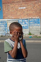 """A young boy tries to hold his mask in place as he prays, in Parkwood, Cape Town, South Africa, on Sunday, May 31, 2020. The joint prayer in Afrikaans opened a special chicken lunch served by the Parkwood Community Upliftment (PCU) project. The youth organization, which normally feeds children as part of an after-school care program, has been feeding children, the elderly, and many other hungry people, in this poverty-stricken area in the Cape Flats since lockdown started more than two months ago. As the nation moves down to Level 3, on June 1st, CPU founder Max Amansure says the organization will continue to feed people. Often it's """"only"""" bread as the organization doesn't have any regular funding. However, as the area has been hard hit by COVID-19, Amansure says he wishes Parkwood could have remained on Level 5 Lockdown. PHOTO: EVA-LOTTA JANSSON"""