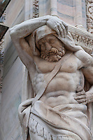 Milan, Italy, Duomo Cathedral - sculpture of a man supporting a stone pillar.