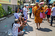 31 JANUARY 2014 - BANGKOK, THAILAND:  A Buddhist monk walks past people lined to receive charity in front of Wat Mangkon Kamalawat during Lunar New Year festivities, also know as Tet and Chinese New Year, in Bangkok. This year is the Year of the Horse. Ethnic Chinese make up about 14% of Thailand and Chinese holidays are widely celebrated in Thailand.     PHOTO BY JACK KURTZ