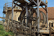 Lifting gear or squirrel cage with double drum and behind, the Chapel Tower and tiled roof of the North Range or Logis Seigneurial, completed 2010, at the Chateau de Guedelon, a castle built since 1997 using only medieval materials and processes, photographed in 2017, in Treigny, Yonne, Burgundy, France. The Guedelon project was begun in 1997 by Michel Guyot, owner of the nearby Chateau de Saint-Fargeau, with architect Jacques Moulin. It is an educational and scientific project with the aim of understanding medieval building techniques and the chateau should be completed in the 2020s. Picture by Manuel Cohen