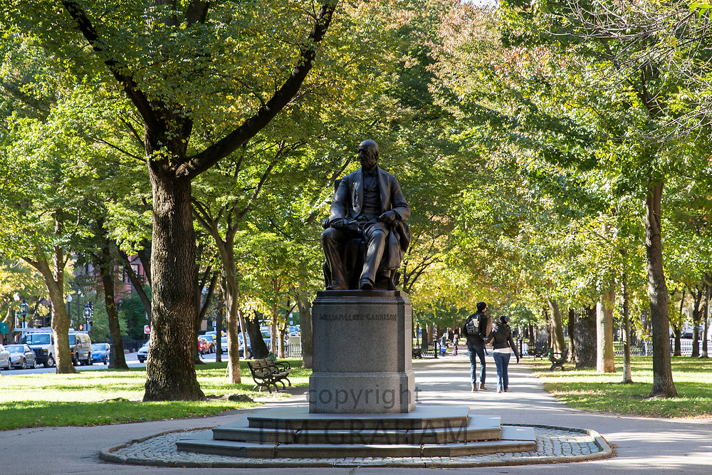 Couple strolling in Commonwealth Avenue Mall near William Lloyd Garrison statue sculpted by Olin Levi Warner, in Boston, USA