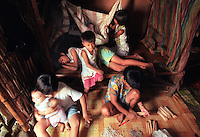 Elpie Sara right (on floor) bundles bamboo skewer sticks that her husband Marcelo Sara sells in Manila to support the family.  Rina, 9, right top, rocks her youngest sibling John Mark, 1, while Leonor, 12, sleeps, and Marife, 5,  moves off the bamboo bed.  Daughter-in-law Jessica Fernandez, left, holds her daughter Princess--Elpie and Marcelo s only grandchild.  The Sara s shared this one-room 12 by 15 foot shanty with eight children in Maragondon Philippines. Within two weeks the family moved into the new home they built with help from World Vision and Habitat for Humanity volunteers.(Janet Jensen/The News Tribune)
