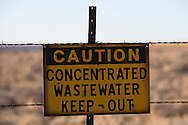 "Water warning sign across from the San Juan Generating Plant just outside of Farmington, New Mexico in the Four Corners region, deemed an 'energy Sacrifice Zone,"" by the Nixon administration, is one of America's largest coal plants."