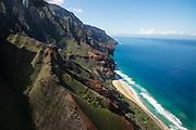 Kalalau Beach & Na Pali Coast sea cliffs seen via helicopter over island of Kauai, Hawaii, USA.
