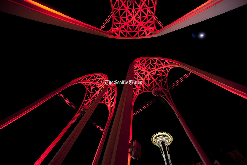 Looking a little like the tendons of heart valves, Pacific Science Center's arches bask in red light, with the Space Needle in the background.<br />