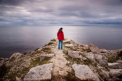 Young woman standing on the coastal path, looking out to sea, Isle of Portland, Dorset, England, UK.