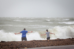 © Licensed to London News Pictures. 01/01/2014. Southsea, UK. People braving the weather conditions as strong winds hit the coast of Southsea, Hampshire, UK on New Years Day 2014. Photo credit : Rob Arnold/LNP
