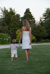 woman walking with little boy on a lawn