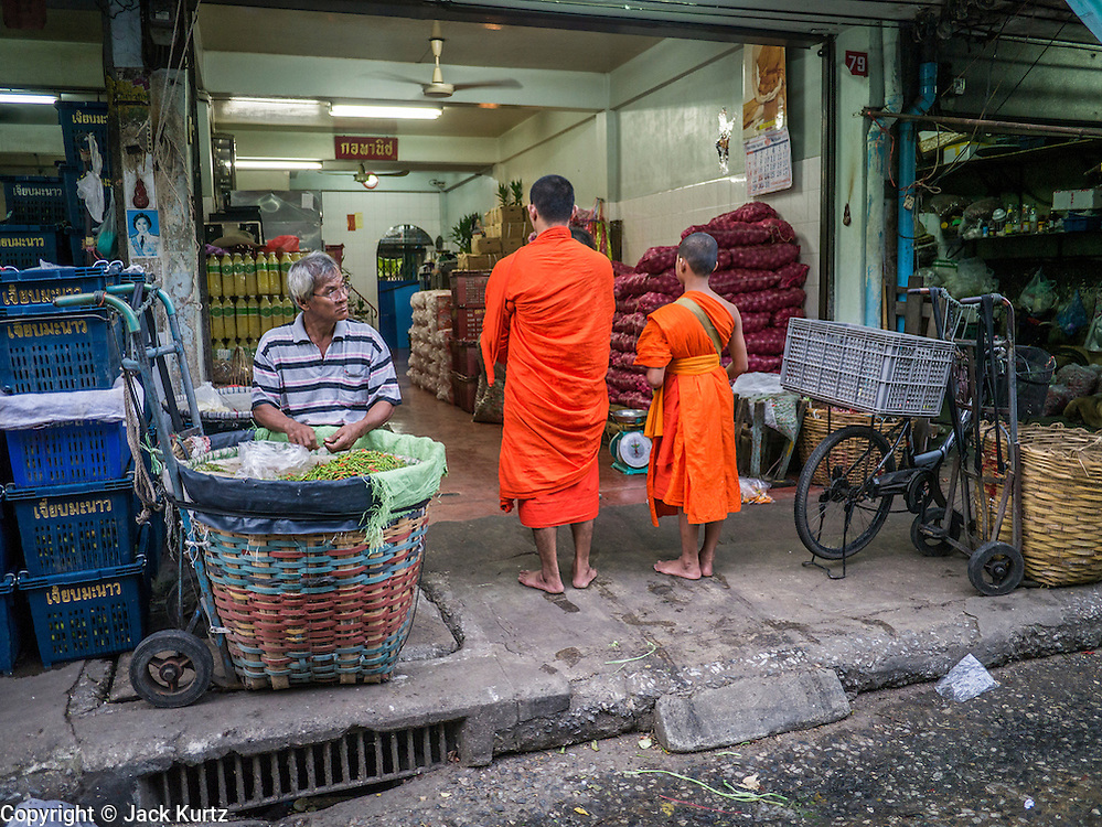 19 OCTOBER 2012 - BANGKOK, THAILAND:  Buddhist monks collect alms in the produce section of the Bangkok Flower Market. The Bangkok Flower Market (Pak Klong Talad) is the biggest wholesale and retail fresh flower market in Bangkok.  The market is busiest between 3:30AM and 6AM. Thais grow and use a lot of flowers. Some, like marigolds and lotus, are used for religious purposes. Others are purely ornamental.          PHOTO BY JACK KURTZ