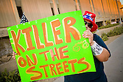 11 OCTOBER 2010 - PHOENIX, AZ:  A woman pickets the Phoenix police headquarters Monday night. About 300 people gathered at the Phoenix Police Department headquarters building Monday night to protest the shooting of Daniel Rodriguez and his dog. The officers responded to a 911 call made by Rodriguez' mother. A scuffle ensued when they arrived and Phoenix police officer Richard Chrisman shot Rodriguez, who was unarmed, and his dog. Chrisman then allegedly filed a false report about the event. He has been arrested on felony assault charges. The event has angered some in the Latino community and they have held a series of protests at the police headquarters. They want Chrisman charged with murder.    Photo by Jack Kurtz