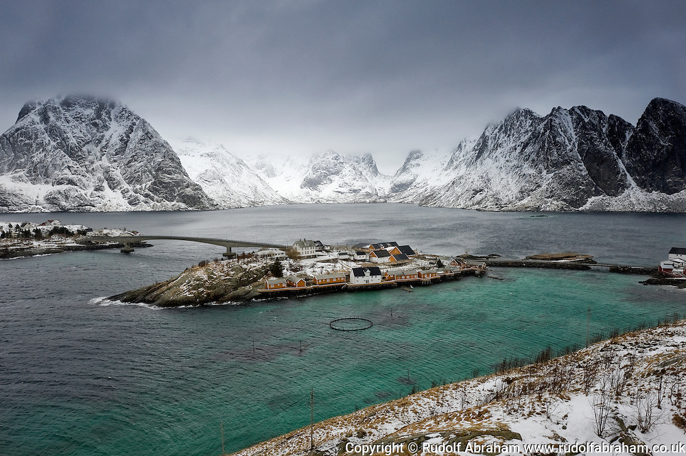 The mountains surrounding Reinefjord in winter, and rorbuer (traditional fisherman's cottages) at Sakrisoy, from Olenilsoy, Moskenesoya, Lofoten Islands, Arctic Norway