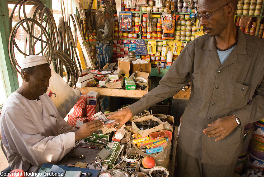 """Trader Mohammed Abdulrahman, from El Muglad (left), gives change to a customer at his hardware store in the market of Abyei. Recent developments in Abyei town are making people settle down. """"No one was thinking of using these materials before."""""""