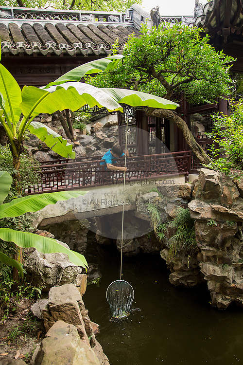 A worker cleans the pond at Nine Lion Pavilion in Yu Yuan Gardens Shanghai, China