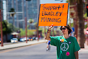 "06 JUNE 2012 - PHOENIX, AZ:   A supporter of US Army PFC Bradley Manning pickets a street corner in Phoenix Wednesday. About 10 people gathered on a street corner in central Phoenix Wednesday to support Manning, who been criminally charged for passing secrets in the ""wikileaks"" case and is awaiting trial in a US Army jail.       PHOTO BY JACK KURTZ"