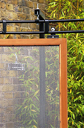 Detail of sliding wire mesh screen in front of outdoor shower. Design: Diarmuid Gavin