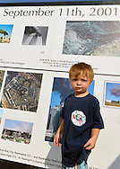 "East Meadow, New York, U.S. 11th September 2013. TIMOTHY HUNTER, 3, of Wantagh, visits the Global War on Terror ""Wall of Remembrance"" a traveling memorial on display in New York for the first time, at Eisenhower Park on the 12th Anniversary of the terrorist attacks of 9/11. Timothy's uncle Joseph G. Hunter, a firefighter in Squad 288 in Maspeth Queens, died during September 11th 2001 terrorist attack, and the nephew is wearing a T-shirt from the 9th Annual Memorial Drill for his Uncle Joseph. The unique 94 feet long by 6 feet high wall has, on one side, almost 11,000 names of those lost on September 11, 2001, along with heroes and veterans who lost their lives defending freedom of Americans over past 30 years. On the wall's other side is a timeline, with photos, covering 1983 to present day."