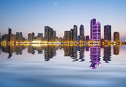 Evening skyline view of modern high-rise apartment buildings on Corniche in Sharjah United Arab Emirates