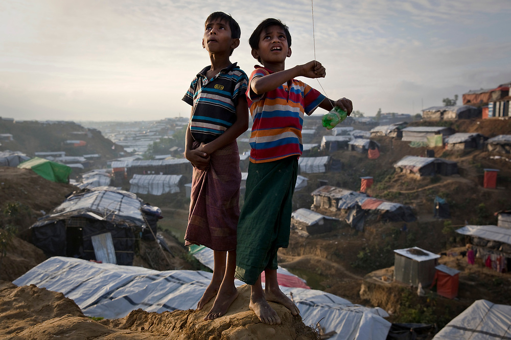 Boys fly a kite on a hill overlooking a refugee camp in Cox's Bazar, Bangladesh, December 12, 2017. More than 670,000 Rohingya, around 60% of them children, have fled Myanmar for Bangladesh since the 25th August 2017.