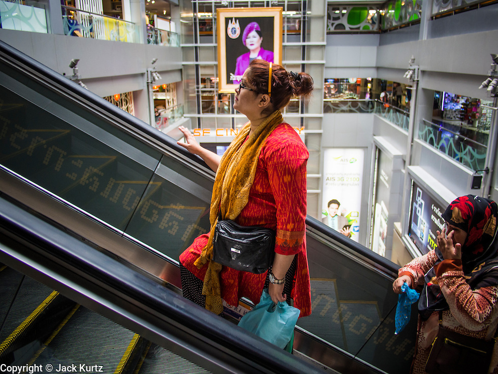 "21 AUGUST 2013 - BANGKOK, THAILAND:    Shoppers ride an escalator in MBK, a large shopping mall in Bangkok. Thailand entered a ""technical"" recession this month after the economy shrank by 0.3% in the second quarter of the year. The 0.3% contraction in gross domestic product between April and June followed a previous fall of 1.7% during the first quarter of 2013. The contraction is being blamed on a drop in demand for exports, a drop in domestic demand and a loss of consumer confidence. At the same time, the value of the Thai Baht against the US Dollar has dropped significantly, from a high of about 28Baht to $1 in April to 32THB to 1USD in August.    PHOTO BY JACK KURTZ"