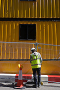 Construction worker secures fencing beneath yellow temporary works offices in central London.