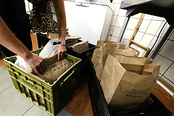 JOHANNESBURG SOUTH AFRICA - MAY 01 Croft & Co staff and owners prepare meals for delivery on May 01, 2020 in Johannesburg South Africa. South Africa moved down to Level 4 of the national lockdown with relaxed restrictions as part of a risk adjusted 5 stage phasing of lockdown measures. This includes allowing of certain restaurants to reopen for trade and prepare hot food as delivered takeaway only. (Photo by Gallo Images/ Dino Lloyd) - NB: PERSONAL DETAILS OBSCURED ON BAGS