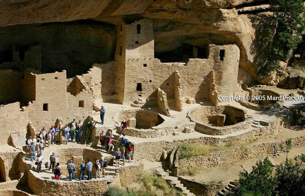 A ranger-led tour makes their way through the Cliff Palace site at Mesa Verde National Park one afternoon. The cliff dwellings at Cliff Palace were discovered in 1888 by cowboys Richard Wetherill and Charlie Mason. The archeological sites found in Mesa Verde National Park, near Cortez, Co., are some of the most notable and best preserved sites in the United States. Mesa Verde offers visitors a spectacular look into the lives of the Ancestral Pueblo people. The culture represented at Mesa Verde reflects more than 700 years of history. From approximately A.D. 600 through A.D. 1300 people lived and flourished in communities throughout the area, eventually building elaborate cliff dwellings in the sheltered alcoves of the canyon walls. Mesa Verde National Park is a U.S. National Park and UNESCO World Heritage Site located in Montezuma County, Colorado, United States. The park occupies 81.4 square miles (211 square kilometers) and features numerous ruins of homes and villages built by the ancient Pueblo people. It is best known for several spectacular cliff dwellings ? structures built within caves and under outcroppings in cliffs ? including Cliff Palace, which is thought to be the largest cliff dwelling in North America..(MARC PISCOTTY/ © 2005)