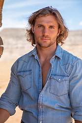 good looking man with long brown hair and blue eyes in a denim shirt