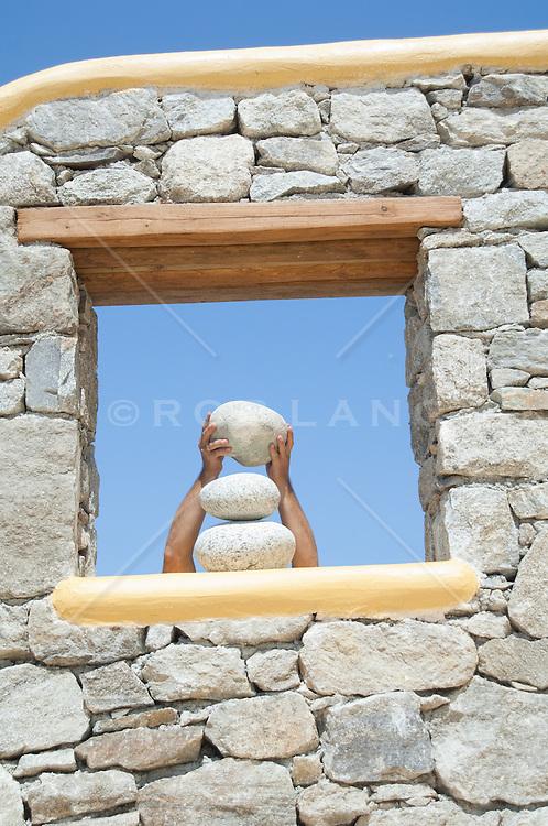 detail of man's hands stacking rocks in a window in Greece